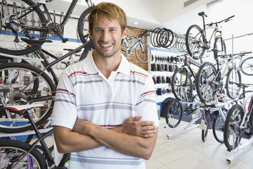 Store manager in bicycle shop smiling at camera