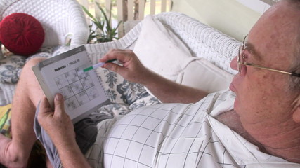 Man sitting and relaxing on his verandah playing sudoku.