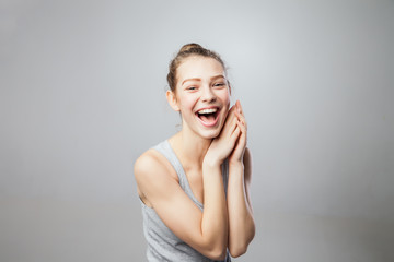 pretty young excited woman, isolated against grey  background