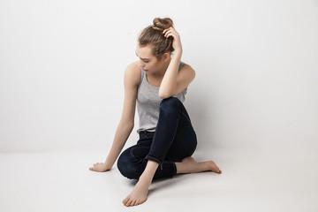 Beautiful melancholic girl sitting on the floor .