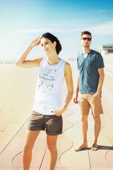 Young tourist couple standing on a beach boardwalk