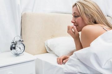 Anxious blonde looking her alarm clock
