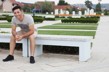 Smiling man sitting on a park bench