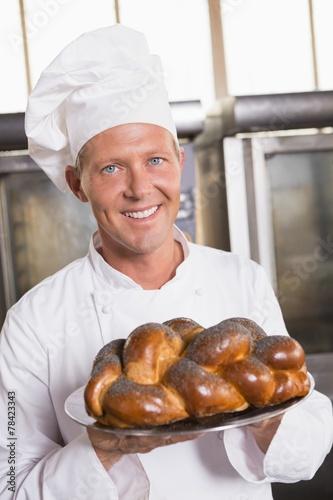 Baker showing freshly baked loaf - 78423343