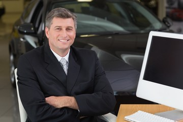 Smiling businessman sitting at his desk with arms crossed