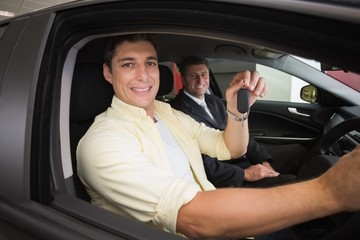 Happy male driver at the wheel sitting in his car