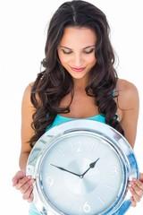 Pretty brunette holding a clock