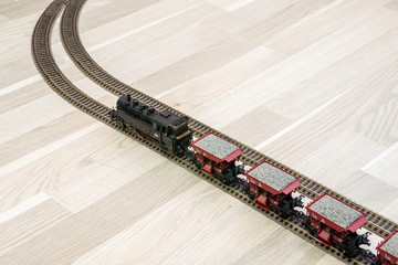 Model steam train on wooden floor, game for kids