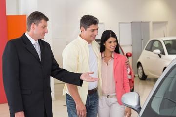 Smiling businessman presenting a car