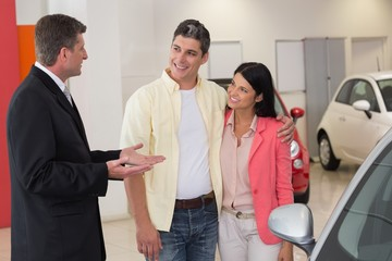 Smiling businessman speaking with his customers