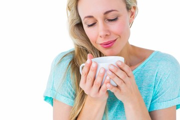 Smiling blonde with hot beverage relaxing