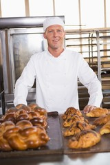 Smiling baker showing board of breads