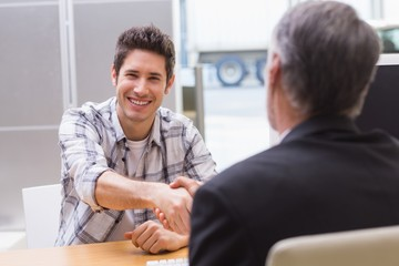 Smiling customer shaking a salesman hand