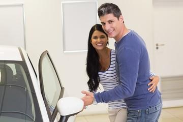 Couple holding a car door handles