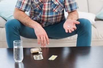 Man sitting on sofa holding pills