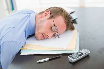 Tired businessman with stack of files on desk