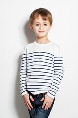 Cute little boy standing on background