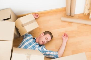 Man lying under fallen boxes