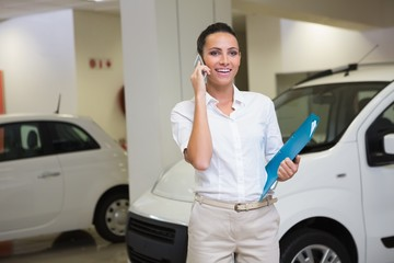 Smiling businesswoman on the phone holding folder