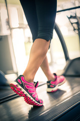 Fitness girl running on treadmill. With muscular legs in gym.