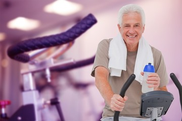 Composite image of senior man on exercise bike