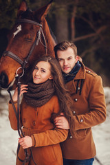 outdoor fashion portrait of young sensual couple and horse