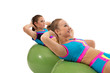 Smiling girls pump abdominals on fitness balls