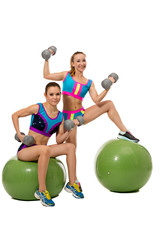 Two smiling girls exercising with dumbbells