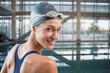 Composite image of pretty swimmer by the pool smiling at camera