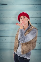 Composite image of blonde in winter clothes blowing kiss