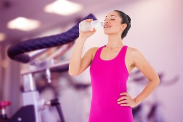 Composite image of fit woman taking a drink