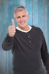 Composite image of casual man showing thubms up at camera