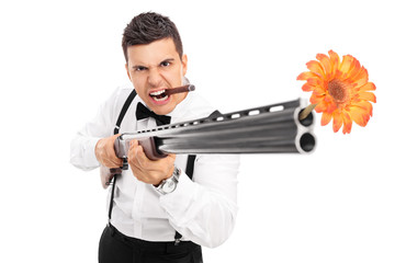 Angry guy shooting flowers from a rifle