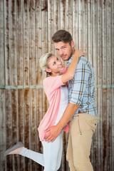 Composite image of handsome man hugging his girlfriend