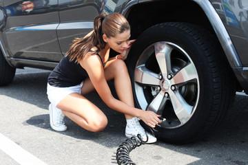 Junge Frau mit Reifenluftdruckprüfer