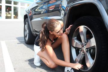 Frau kontrolliert Reifendruck