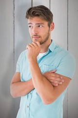 Composite image of handsome young man thinking with hand on chin