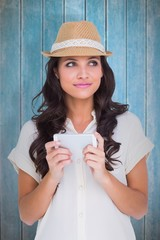 Composite image of pretty brunette holding her phone