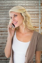 Composite image of attractive blonde talking on her smartphone