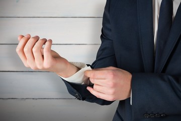 Composite image of businessman adjusting his cuffs on shirt