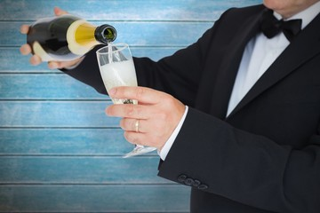 Composite image of man in suit pouring champagne