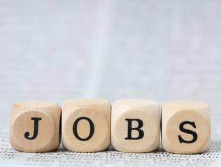 Holzwürfel mit dem Wort Jobs auf einer Zeitung