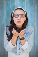 Composite image of brunette blowing kiss