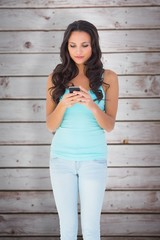 Composite image of casual brunette sending a text