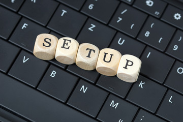 Tastatur und Holzwürfel mit dem Wort Setup