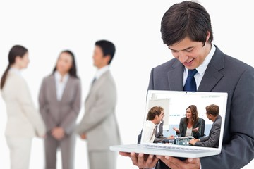 Salesman showing laptop screen with team behind him