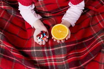 pills and orange in hands