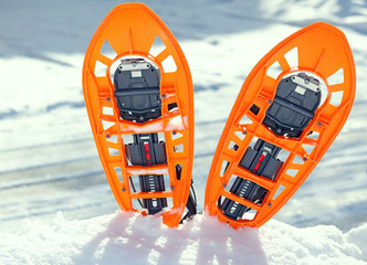pari of orange modern snowshoes in the mountain