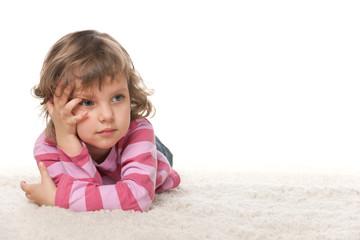 Pensive little girl on the white carpet