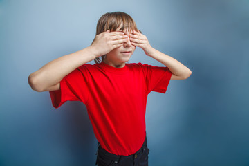 boy teenager European appearance in a red shirt closed eyes with